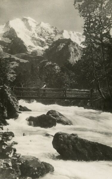 A wooden bridge over the raging torrent of the Lutschine River with the magnificent spike of the Jungfrau Mountain rising up behind. Picture from a postcard set of views of Interlaken in the Canton of Bern, Switzerland and local countryside scenes