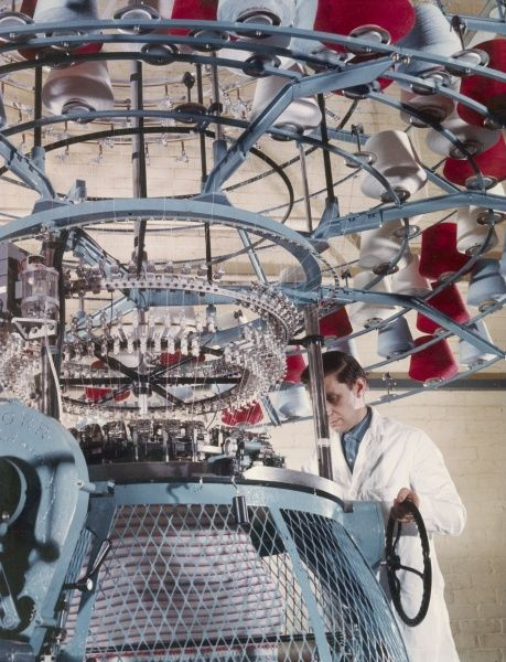 An employee checks a machine which is collecting different coloured wool yarns onto large rolls at Patons & Baldwins factory in Darlington. Patons & Baldwins was a leading British manufacturer of knitting yarn.Photograph by Heinz Zinram