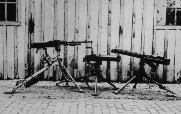 Three machine guns on their tripods on display in front of a shed during the First World War
