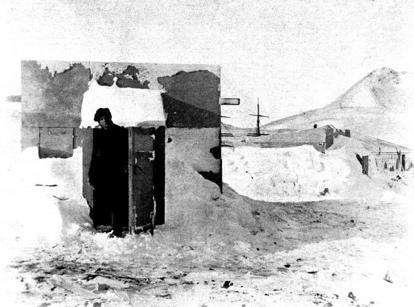 Photograph showing Mr. Bernacchi standing in the doorway of the 'Magnetic Hut' during the National Antarctic Expedition of 1901-4