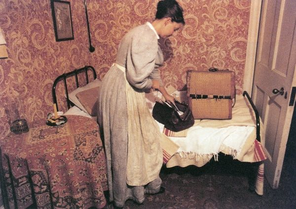 Unable to cope with the drudgery of being an Edwardian servant, the scullery maid packs her bags in her bedroom. Date: early 1900s (re-enactment)