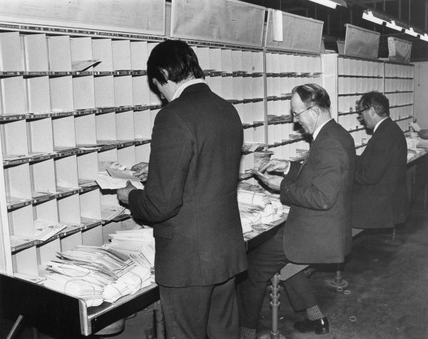 Postal workers at the General Post Office (Britain), manually sorting mail into pigeon holes
