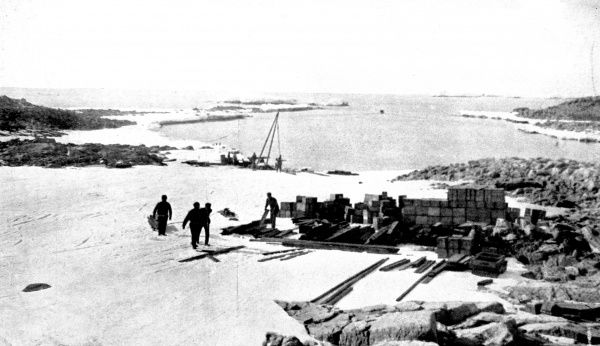 Photograph of the main base of Australian Antarctic Expedition of 1911-14, Adelie Land, Antarctica, 1913. The stores and wireless telegraph poles can be seen in the foreground, with the harbour in the background