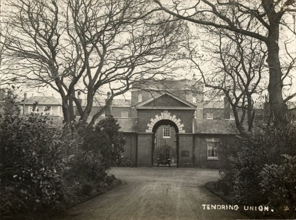 The main entrance of the Tendring Union workhouse at Tendring Heath, Essex. A car and bicycle can be seen. The building, designed by George Gilbert Scott and William Bonython Moffatt, was opened in 1838. It later became known as Heath Hospital