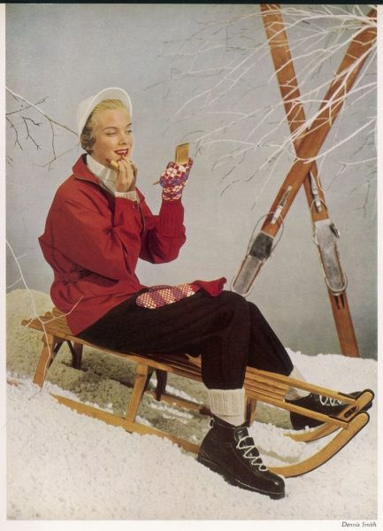 All ready for a day's winter sport, a woman applies the last completing touch of lipstick. Her equipment includes white knitted cap and sweater, red Grenfell ski jacket, navy vorlages and ski socks all from Lillywhites as are also the Henke boots