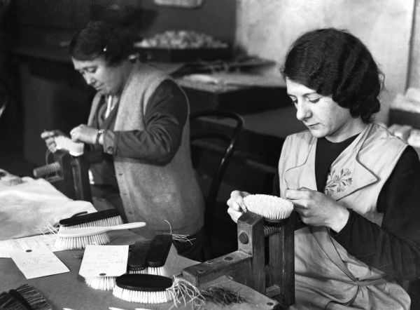 These women are fixing bristles into ivory hairbrush handles. Date: February 1933