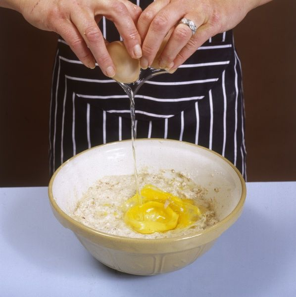 Cracking eggs into a cake mix in a baking bowl. Date: 1980