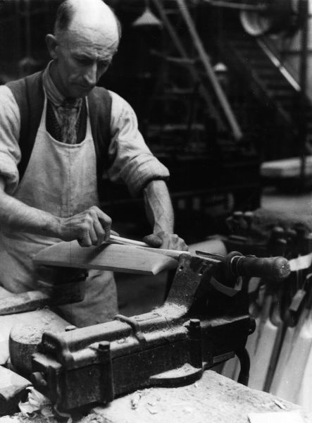 A cricket bat maker at Accrington, Lancashire, England, who is using the shin bone of a reindeer to smooth of a bat. Date: 1930s