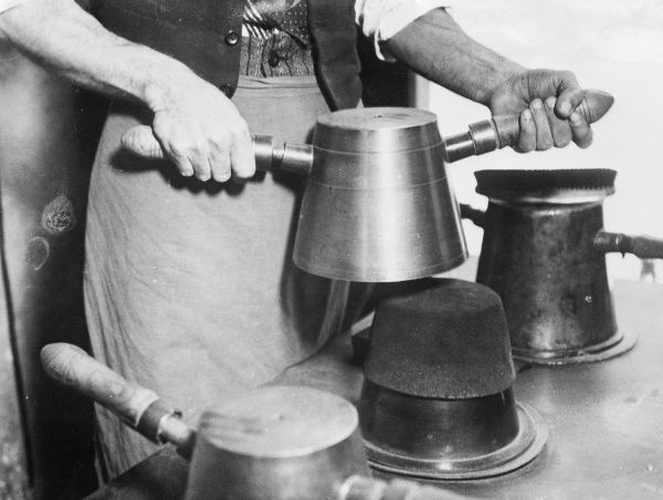 Making a fez or tarboosh (from the Persian 'sar', meaning head and 'poosh', cover) worn by East Mediterranean Muslim men, which originated in Fez, Morocco, North Africa. Date: 1930s