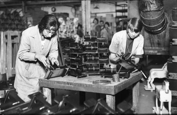 Two skilled young women making toy locomotives in a British factory. The engines are carefully cut and bent into shape and then hand painted