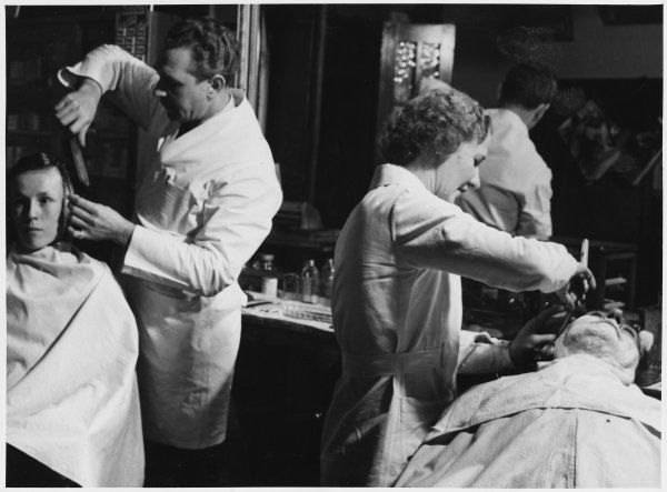 A female barber wet shaves a gentleman while her male colleague cuts hair