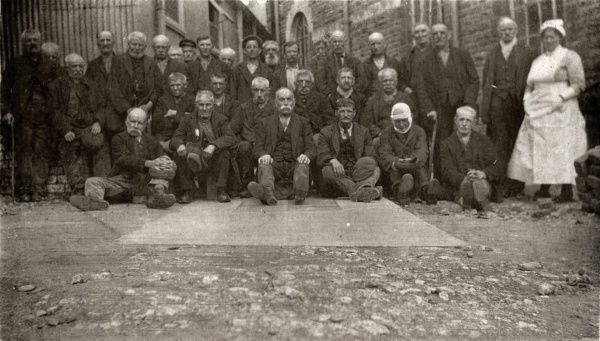 A group of elderly male inmates, accompanied by a nurse, at the Cardiff Union workhouse located on Cowbridge Road, Cardiff