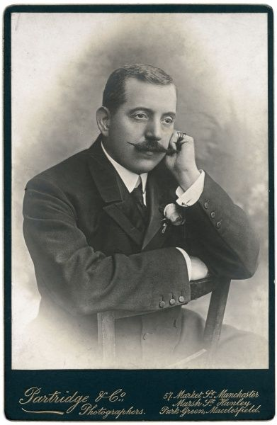 Portrait photograph of a gentleman with a moustache leaning on the back of a chair