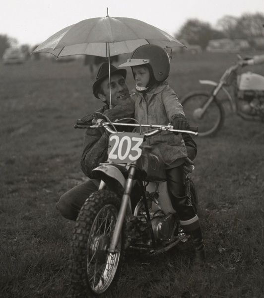 A man gives his son a bit of advice under an umbrella before the boy sets off on his junior sized motorcycle