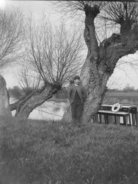 An Edwardian man poses by a tree on a canal bank, with a canal boat called the Rambler behind him, somewhere in South Wales