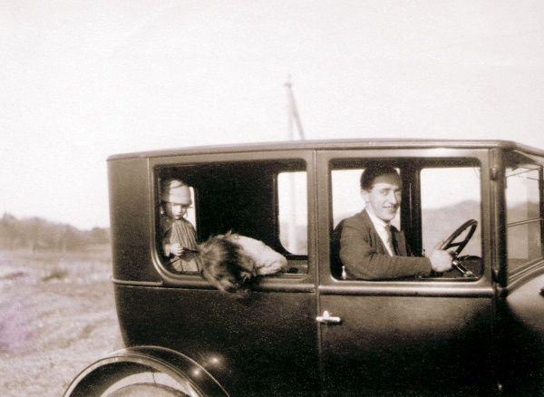 A smiling man driving a car with two young children in the back. Date: circa 1920