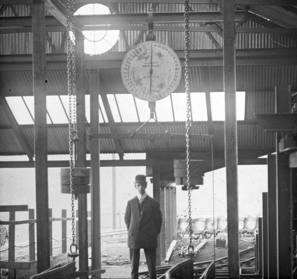 A smartly dressed man (Herbert Saunders) standing under a coal weighing machine at Llanerch Colliery near Pontypool in South Wales