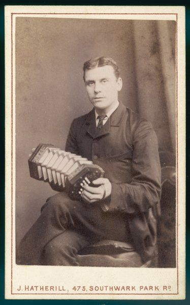 A young man is photographed playing his concertina