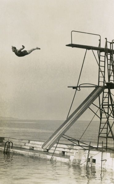 A man dives from a diving board into an outdoor pool at an unidentified seaside resort. Date: circa 1930s