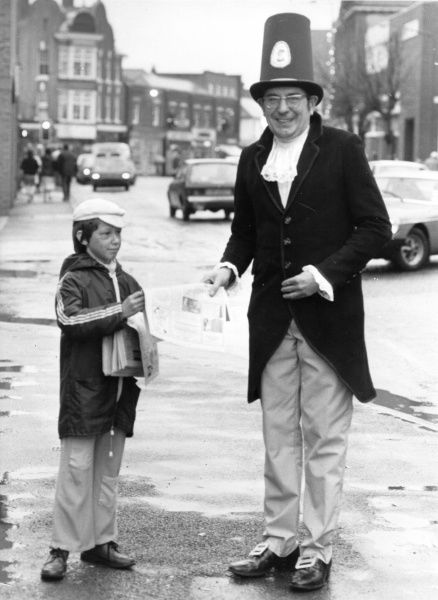 A man dressed up in vaguely Victorian gear for Dickens Day, to celebrate the life and work of the novelist Charles Dickens. He is buying a newspaper from a little boy who also has a Dickensian look about him, apart from his modern anorak!