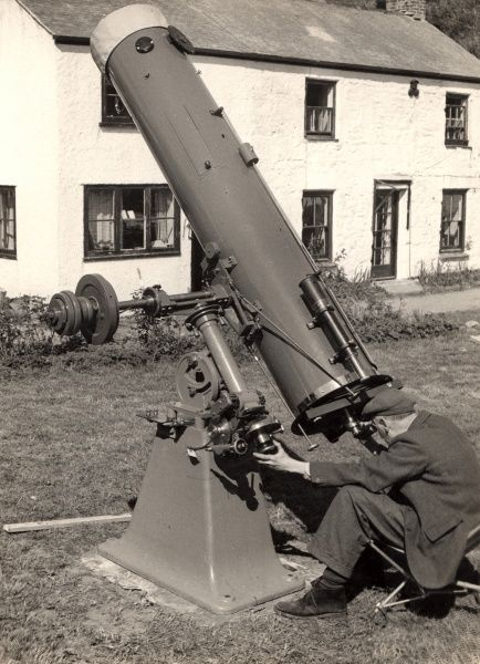A man in a flat cap sits and looks through an unfeasibly large telescope which appears to be installed in his back garden. Bet his wife was pleased about that purchase