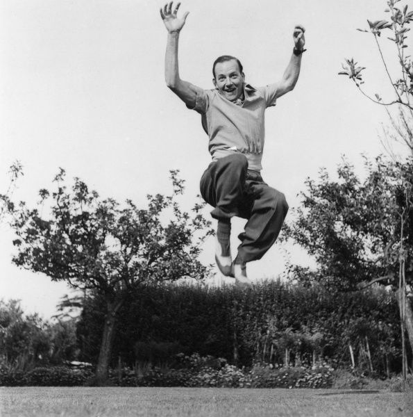 An athletic man leaping high into the air in a garden.  circa 1940s