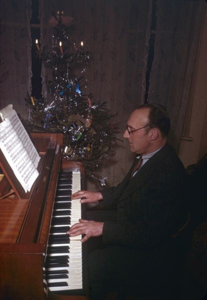 A man playing a piano with a decorated Christmas tree at his side. Three of the candles are lit. Photograph by Heinz Zinram