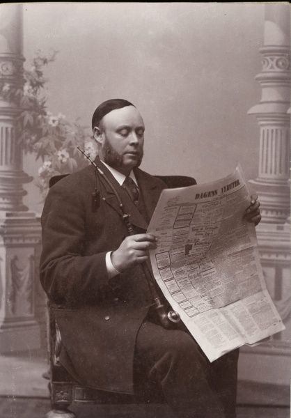 Reading the newspaper with his long pipe in his hand. 1910. Date: 1910