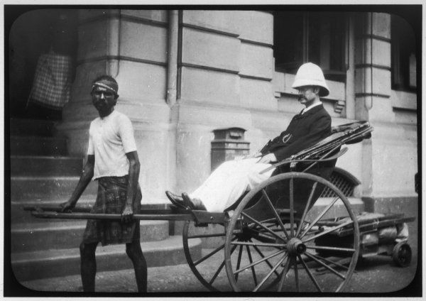 A man wearing a pith helmet being transported by rickshaw, probably in India