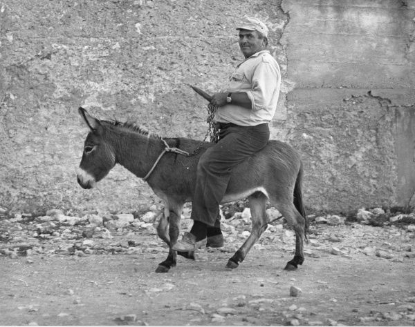 A man riding a small donkey which is quite possibly smaller than he is!