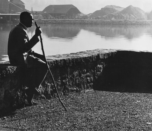 A man with a long stick sitting on a wall, looking out over a stretch of water