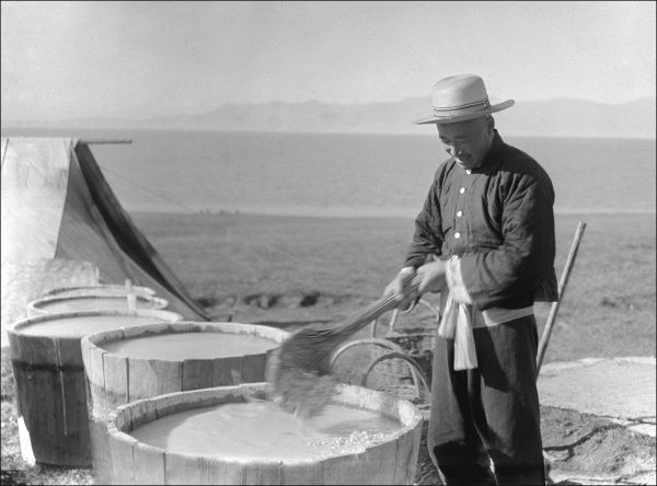 A man stirring vats of liquid in the open air in Kashgar, western China