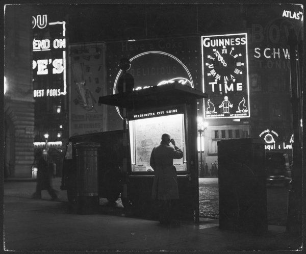 A man in a raincoat studies the Westminster City Guide map at night in Piccadilly Circus