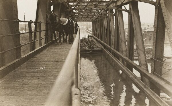A horse-towed coal barge crossing the unique structure of the Barton Swing Aqueduct, carrying the Bridgewater Canal across the wider span of the Manchester Ship Canal - opened in 1893