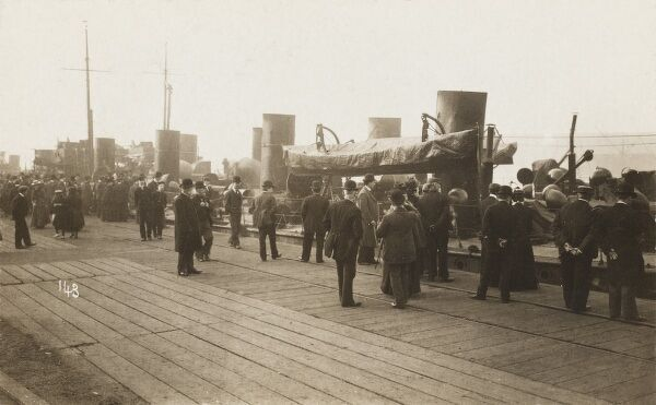 Grandees and dignitaries stand on the quayside and admire the steamships moored in a new dock for the Manchester Ship Canal, opened earlier in the day