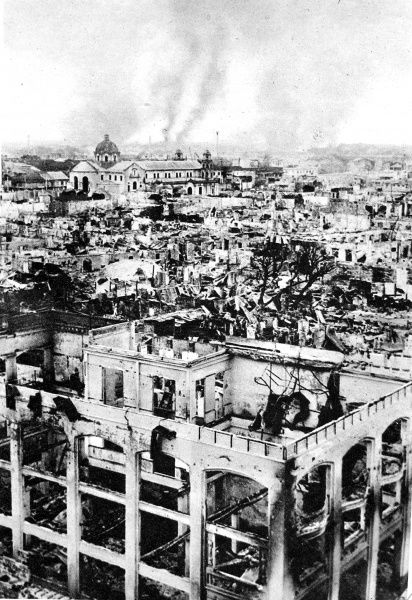 Photograph showing Manila, the Philippine capital, on fire (in background) and with the ruins of gutted buildings in the foreground, during fighting between Japanese and American forces in February 1945