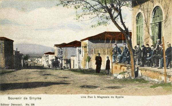 A street at Manisa (Magnesia du Sypile), close to Izmir, Turkey with a group of men sitting outside a Mosque