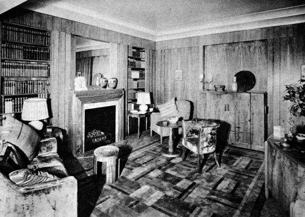 A man's study, with walls panelled in English walnut ply. A simple style without mouldings or enrichments, lighting arranged purely for books and reading. The new British furniture, a complete home in the modern manner. An exhibition at Waring and Gillow