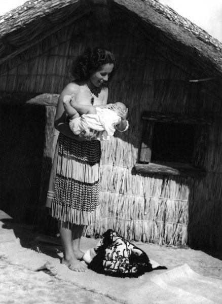 How Maori mothers carry their babies : 'You hold the baby in your arms, like this', says Lena. Baby, self conscious, twiggles his toes! New Zealand. Date: circa 1940