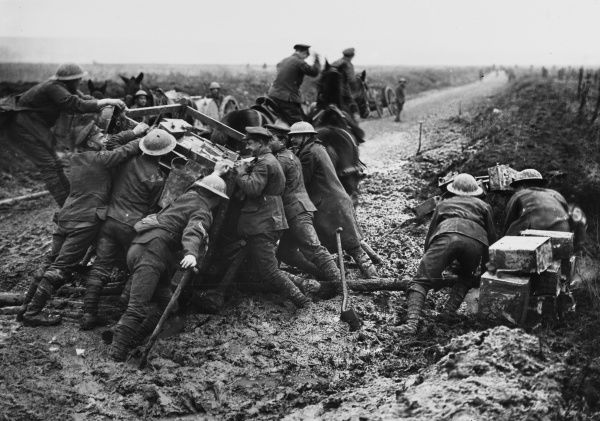 British soldiers pushing a water cart out of a mud filled shell hole near Marcoing during the Battle of Cambrai on the Western Front in France during World War I in November 1917