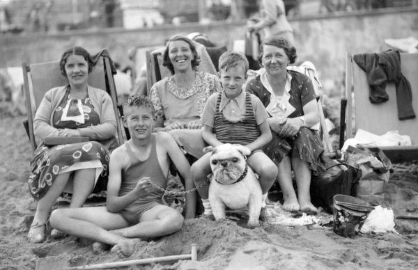 On the beach at Margate: three ladies sit in deckchairs, while two boys in bathing costumes sit, one on the sand, one astride a toy bulldog