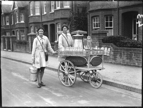 Two Margate milk girls working for E. Orchin, wheeling a cart of fresh milk along a street of fine Edwardian houses