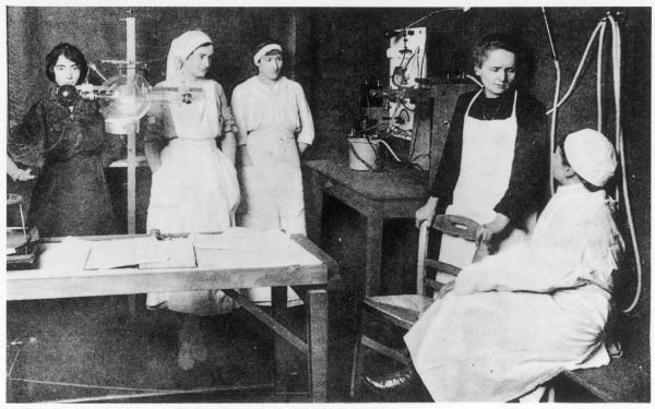 MARIE CURIE explains to a group of nurses the potential benefits of radium treatment