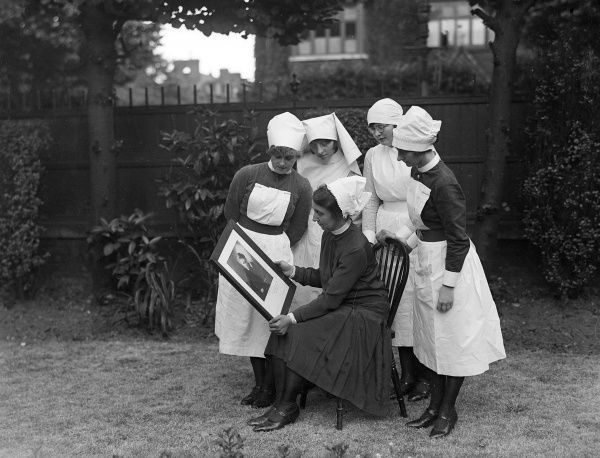 A group of French nurses of the Marie Curie Hospital, Paris, France, admiring a framed picture of their patron and heroine, Marie Curie. Date: early 1930s