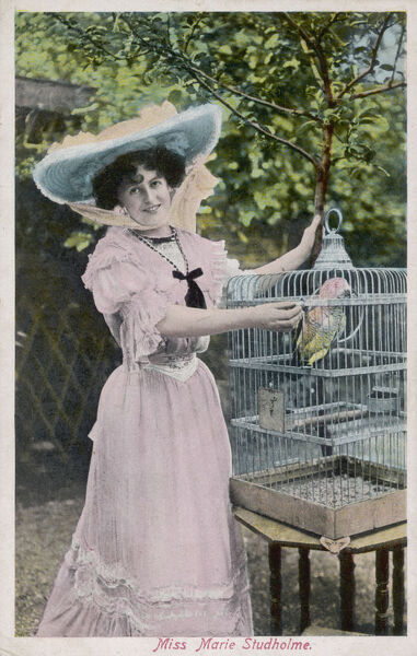 The popular actress Marie Studholme poses with her pet parrot in its cage