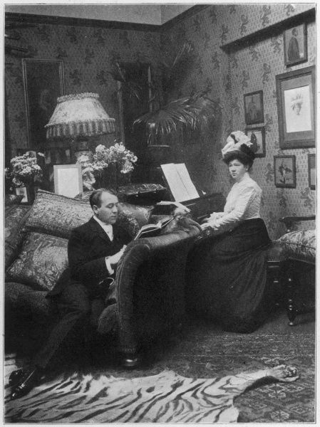 "The ""charming"" Miss Marie Tempest at home, playing the piano in fact, while her husband Cosmo Stuart reads with his shiny shoes on a tiger skin rugs"