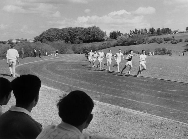 A group of runners approach a corner during a race at Marlborough College. Date: 1950s
