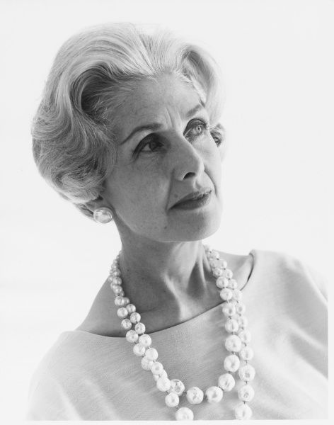 Head and shoulders portrait of a mature woman wearing a large beaded necklace