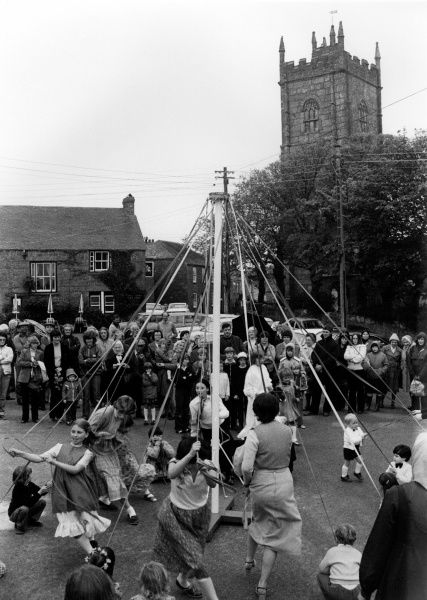 Adults and children dancing round a maypole in the village of Paul, near Penzance in Cornwall, with the tower of the parish church on the right. A crowd of people stand watching them
