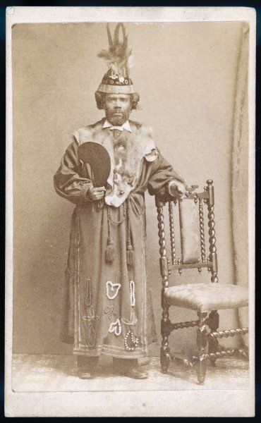 A man wearing a ceremonial costume of long robe and hat decorated with beads and the pelt of an animal, holds a cutting implement. Possibly a member of a Secret Society